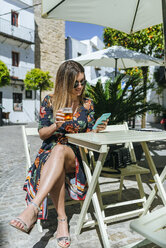 Spain, Cadiz, Vejer de la Frontera, young woman sitting at street cafe with glass of beer looking at phone - KIJF02469