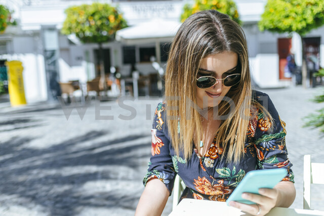 Spain, Cadiz, Vejer de la Frontera, young woman sitting at street cafe  looking at mobile phone - KIJF02472