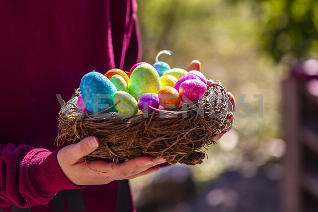 Girl holding Easter nest with colorful Easter eggs - SARF04196 - Sandra Roesch/Westend61