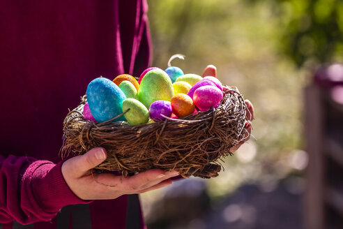 Girl holding Easter nest with colorful Easter eggs - SARF04196