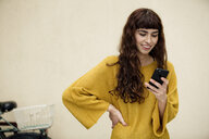 Portrait of smiling young woman looking at cell phone - FLLF00082