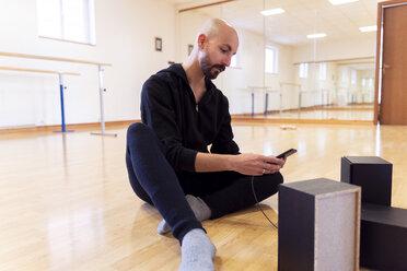 Ballet dancer using cell phone in ballet studio - FMOF00460