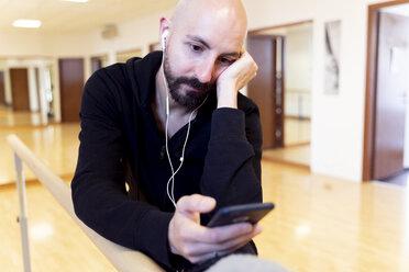 Ballet dancer using cell phone in ballet studio - FMOF00463