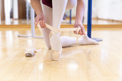 Close-up of ballet dancer putting on shoes - FMOF00472
