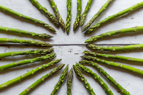 Green asparagus spears building heart on wood - SARF04203