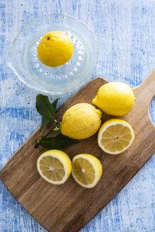 Lemon halves, whole lemon on wooden board and a lemon squeezer - GIOF05894
