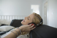 Woman with headphones relaxing listening to music sofa - HEROF32589