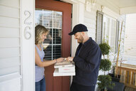 Woman signing for delivery at front door - HEROF32625