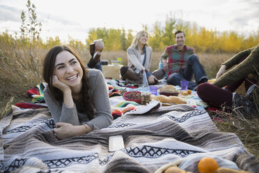 Smiling woman laying on picnic blanket in field - HEROF32634