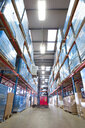 Warehouse worker lifting boxes from shelf with forklift - JUIF00649