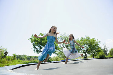 Playful, carefree barefoot girls in dresses playing on trampoline in sunny backyard - FSIF03793