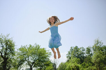 Carefree girl in dress jumping for joy in sunny backyard - FSIF03799