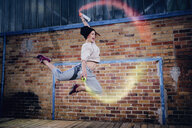 Female modern dancer performing with spray paint cans - FSIF03805