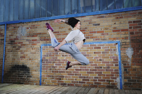 Female modern dancer performing against brick wall - FSIF03817