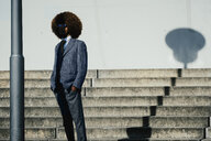 Portrait cool, well dressed young man with afro at urban steps - FSIF03871