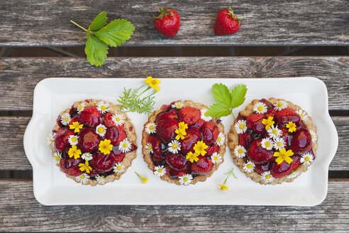 Homemade strawberry heart tartlets with daisy flowers and golden marigold, edible flowers, dark wood - GWF06024