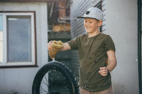 Happy boy cleaning bmx bike on yard - VPIF01194