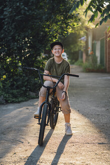 Portrait of smiling boy with bmx bike on road - VPIF01197