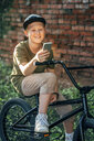 Smiling boy with bmx bike using cell phone - VPIF01206