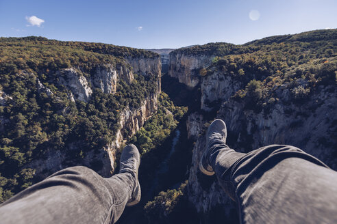 Spain, Navarra, Irati Forest, man's legs dangling above landscape with gorge - RSGF00129