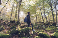 Spain, Navarra, Irati Forest, young woman standing in lush forest - RSGF00135