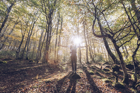 Spain, Navarra, Irati Forest, young man standing in lush forest with outstretched arms - RSGF00138