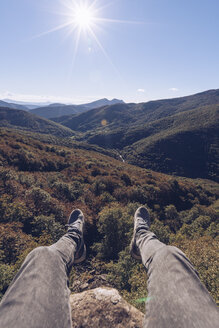 Spain, Navarra, Irati Forest, man's legs dangling above forest landscape in backlight - RSGF00141