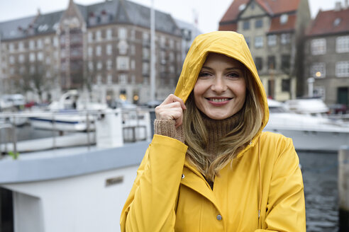 Denmark, Copenhagen, portrait of happy woman at city harbour in rainy weather - ECPF00623