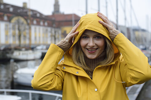 Denmark, Copenhagen, portrait of happy woman at city harbour in rainy weather - ECPF00626