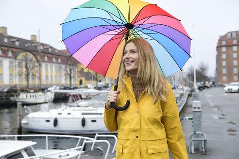Denmark, Copenhagen, happy woman with colourful umbrella at city harbour - ECPF00632
