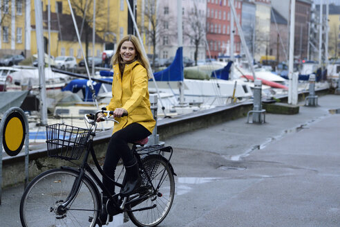 Denmark, Copenhagen, happy woman riding bicycle at city harbour in rainy weather - ECPF00647
