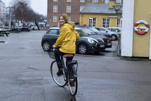 Denmark, Copenhagen, happy woman riding bicycle on waterfront promenade in rainy weather - ECPF00650