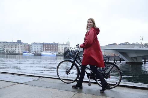 Denmark, Copenhagen, happy woman pushing bicycle at city harbour in rainy weather - ECPF00659