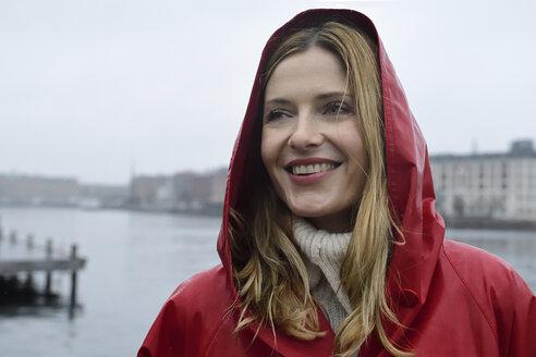 Denmark, Copenhagen, portrait of happy woman at the waterfront in rainy weather - ECPF00665