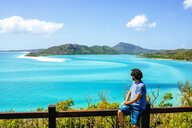 Australia, Queensland, Whitsunday Island, man looking at Whitehaven Beach - KIJF02478