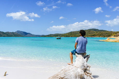 Australia, Queensland, Whitsunday Island, man sitting on log at Whitehaven Beach - KIJF02481