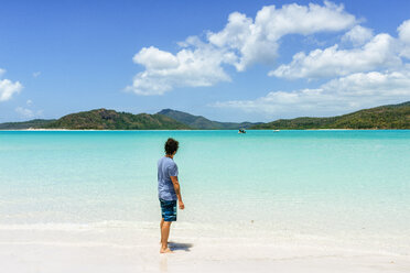 Australia, Queensland, Whitsunday Island, man standing at Whitehaven Beach - KIJF02484