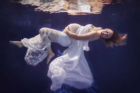 Pregnant woman wearing white dress under water - STBF00277