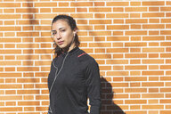 Portrait of sporty young woman with earphones at a brick wall - WPEF01432