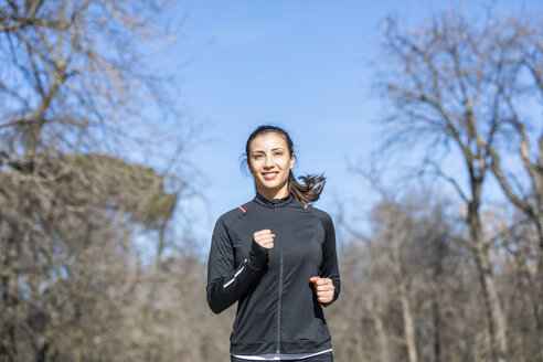 Smiling young woman jogging in park - WPEF01435