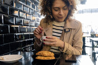 Smiling woman looking at cell phone in a cafe - FMOF00482
