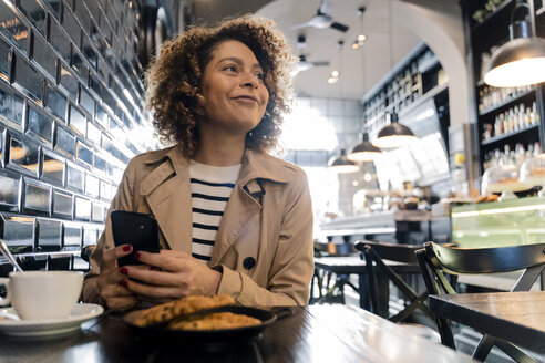 Smiling woman with cell phone in a cafe - FMOF00485