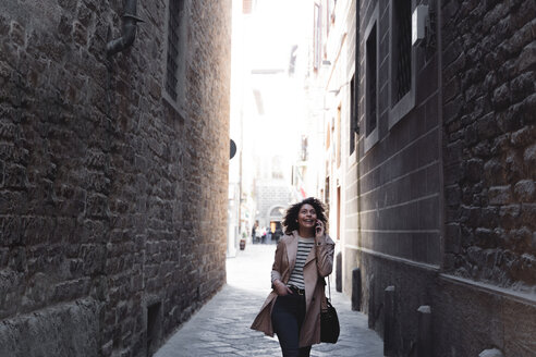 Happy woman talking on cell phone in an alley - FMOF00491