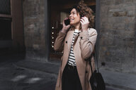 Smiling woman talking on cell phone in an alley - FMOF00494