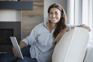 Portrait smiling woman using digital tablet on sofa - HEROF32656
