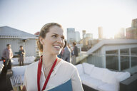 Smiling businesswoman drinking champagne on urban rooftop - HEROF32683