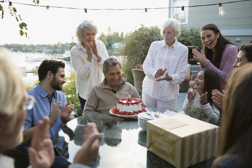 Senior man celebrating birthday family strawberry cake patio - HEROF32713