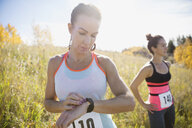 Runner checking wristwatch in sunny field - HEROF32731
