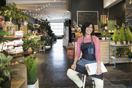 Smiling female shop owner with clipboard in plant shop - HEROF32793
