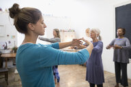 Serene women practicing tai chi in exercise class - HEROF32838